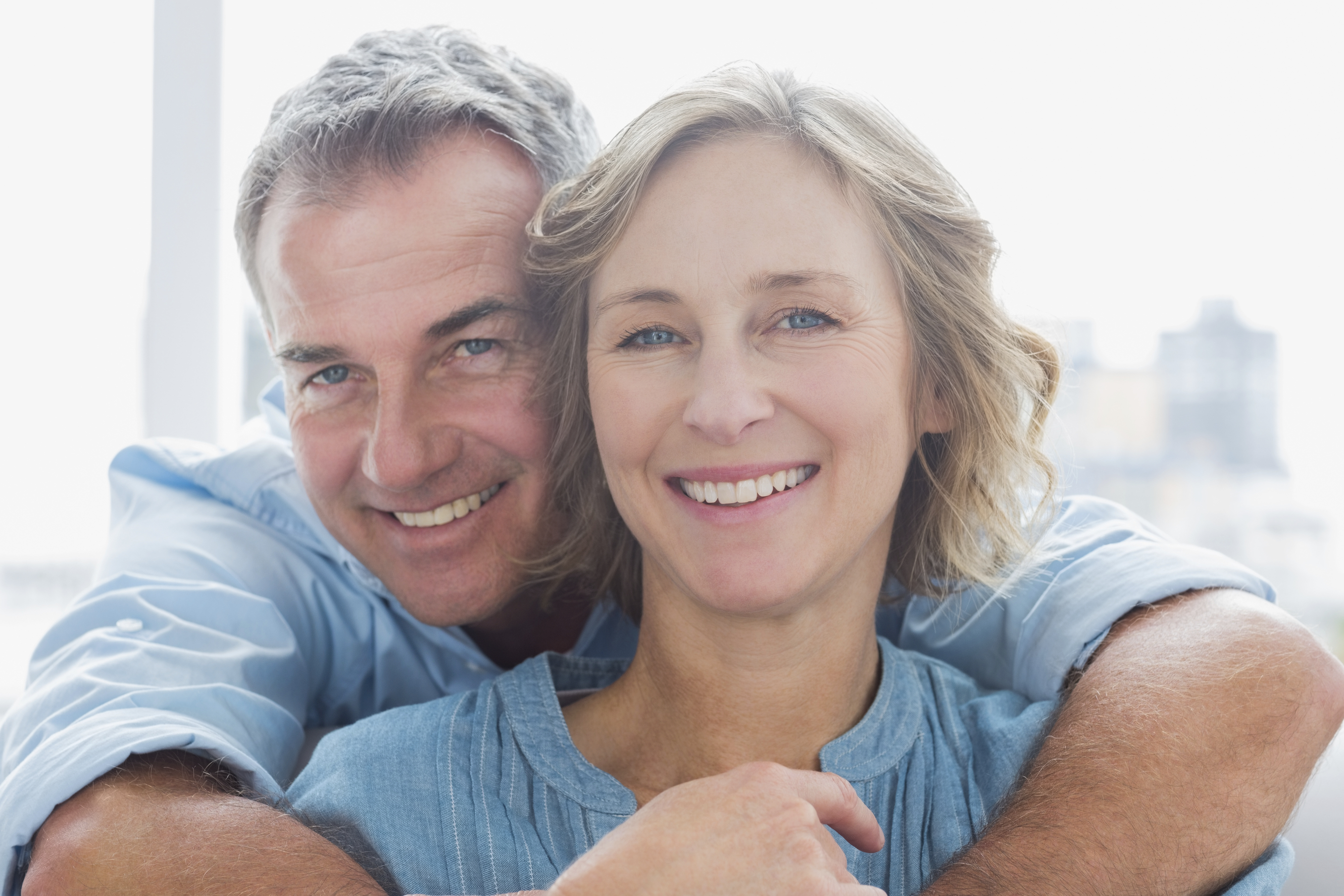 Happy man hugging his wife from behind at home in the living room